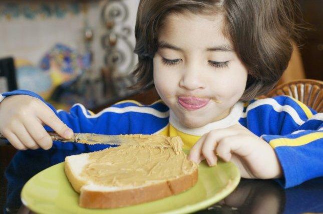 Chłopiec robi kanapkę z masłem orzechowym