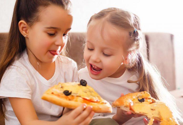 Dwie małe dziewczynki jedzą pizzę