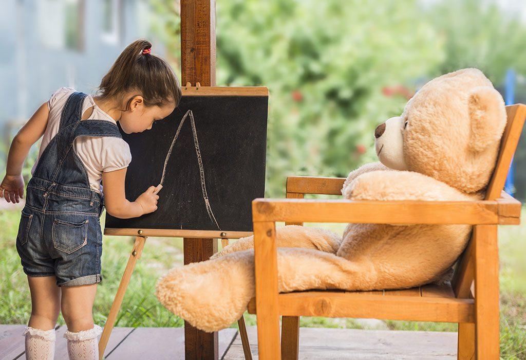 Dziewczyna pisząca na tablicy alfabet