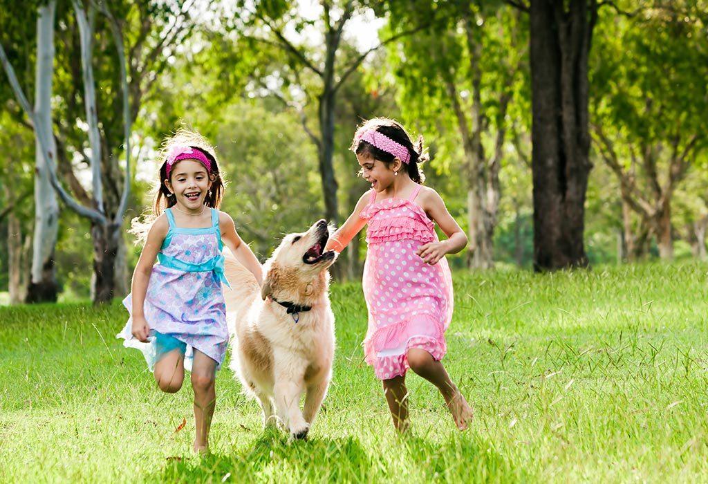 """Dwie dziewczynki bawiące się ze swoim ulubionym psem """"width ="""" 1024 """"height ="""" 700 """"srcset ="""