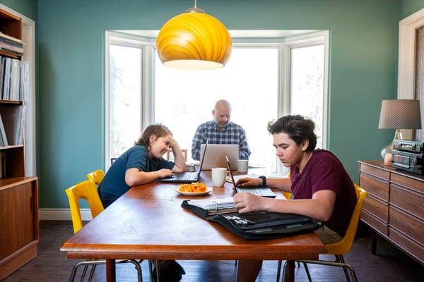 Kobieta pracująca przy stole w kuchni.  Jej nastoletni syn je obok niej.