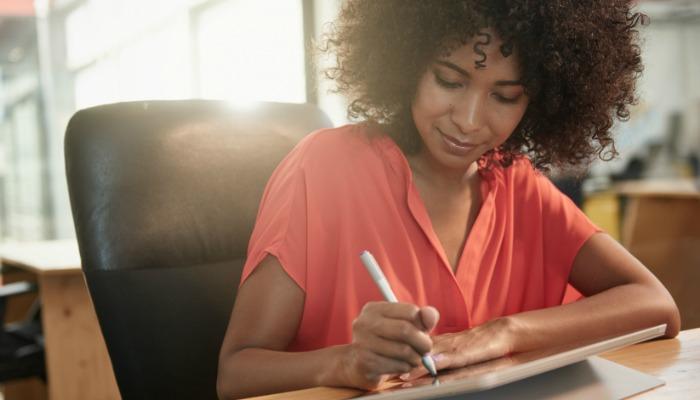 Ujęcie młodej projektantki pracującej na swoim tablecie za pomocą rysika