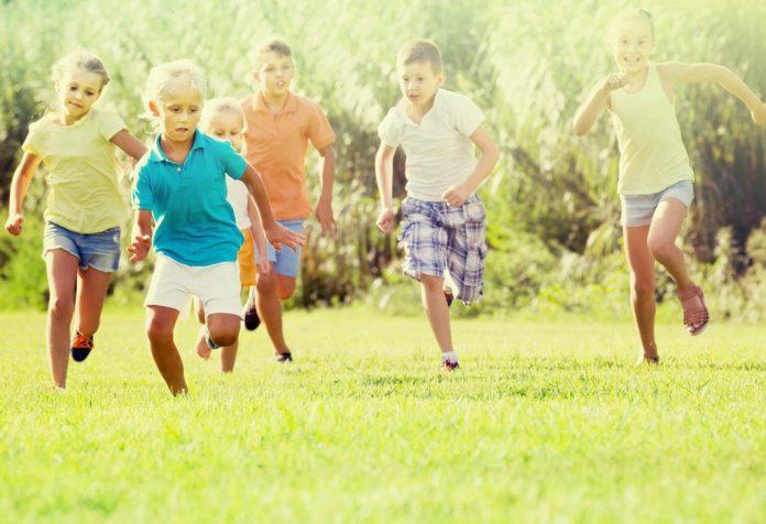 Dzieci biegają po trawie latem