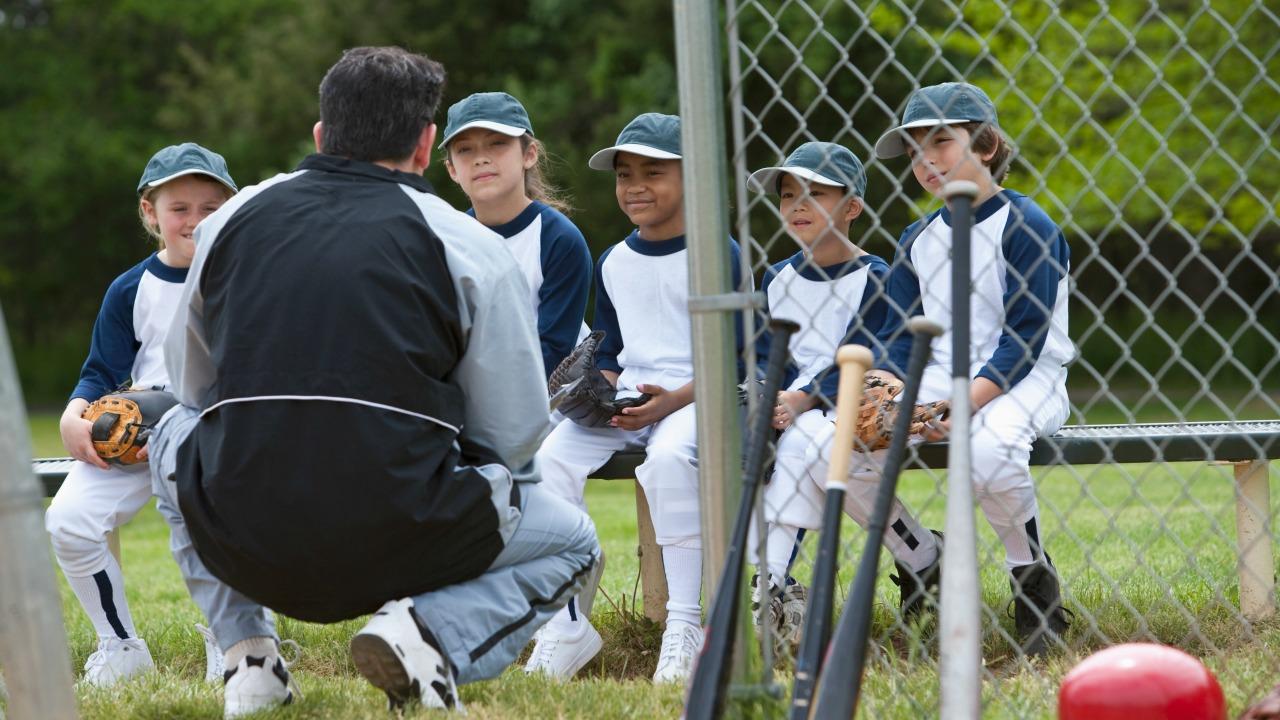 Trener z wielorasowymi dziećmi w drużynie baseballowej