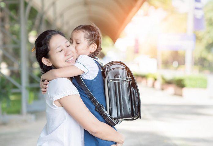 Uczennica w ramionach matki