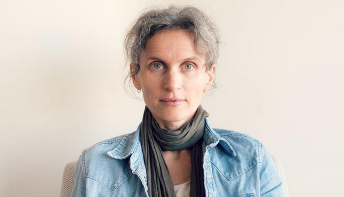 Portret kobiety w średnim wieku z siwymi włosami, dżinsową koszulę i szalik
